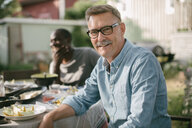Portrait of smiling senior man sitting at table during garden party - MASF10269