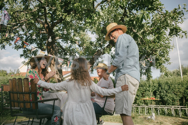 Family applauding while looking at senior man and girl dancing during garden party - MASF10272
