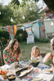 Happy family having lunch at table in backyard during garden party - MASF10275