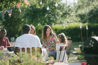 Happy multi-generation family having lunch together at patio during garden party - MASF10278