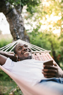 Smiling mid adult man listening music through mobile phone while relaxing on hammock in backyard - MASF10290