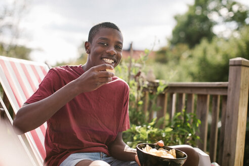 Portrait of smiling boy eating snack while sitting at porch - MASF10293