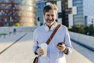 Portrait of smiling mature man with takeaway coffee, headphones and cell phone in the city - GIOF04910