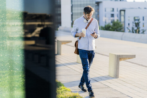 Mature man with takeaway coffee and headphones using cell phone in the city - GIOF04913