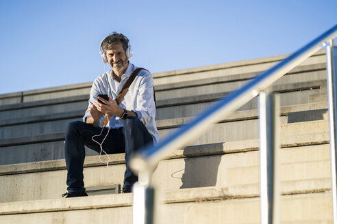 Portrait of smiling mature man sitting on steps with headphones and cell phone - GIOF04919
