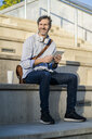 Portrait of smiling mature man sitting on steps with tablet - GIOF04922