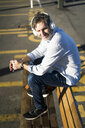 Mature man sitting on a bench listening to music with headphones - GIOF04928