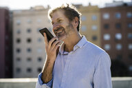 Smiling mature man using cell phone in the city - GIOF04955