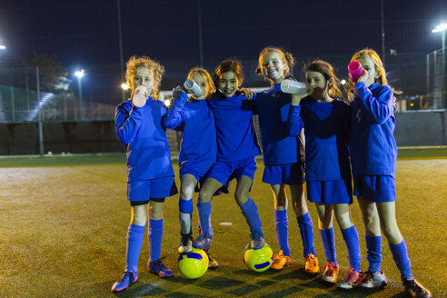 Portrait confident girls soccer team drinking water on field at night - HOXF04196