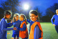 Portrait confident girl soccer player on field with team at night - HOXF04214