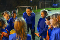 Girls soccer team listening to coach on field at night - HOXF04217