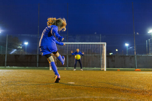 Girl soccer player kicking the ball toward goal - HOXF04220