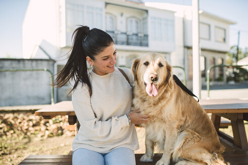 Smiling young woman with her Golden retriever dog resting outdoors - RAEF02226
