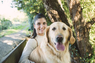 Portrait of a smiling young woman with her Golden retriever dog - RAEF02232