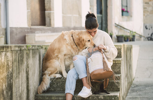 Young woman with her Golden retriever dog on stairs looking in backpack - RAEF02238