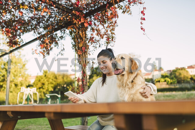 Smiling young woman with cell phone and her Golden retriever dog resting in a park - RAEF02253 - Ramon Espelt/Westend61