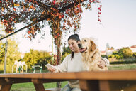 Smiling young woman with cell phone and her Golden retriever dog resting in a park - RAEF02253