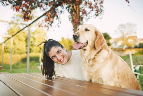 Portrait of happy young woman with her Golden retriever dog resting in a park - RAEF02256