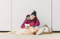 Happy young woman stroking and playing with her golden retriever dog - RAEF02262