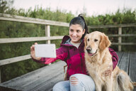 Smiling young woman taking a selfie with her dog - RAEF02268