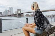 USA, New York City, Brooklyn, young woman sitting at the waterfront with backpack, headphones and tablet - BOYF01121