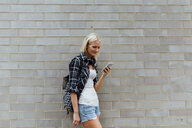 Young woman checking cell phone at brick wall - BOYF01124