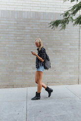 Young woman with cell phone on the go in the city - BOYF01127