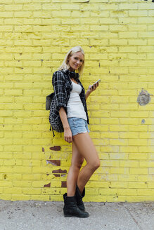 Portrait of young woman with cell phone at yellow brick wall - BOYF01130