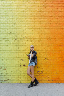 Portrait of young woman with cell phone at colorful brick wall - BOYF01133