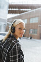 USA, New York City, Brooklyn, smiling young woman listening to music with headphones in the city - BOYF01139