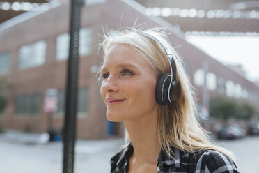 USA, New York City, Brooklyn, smiling young woman listening to music with headphones in the city - BOYF01142