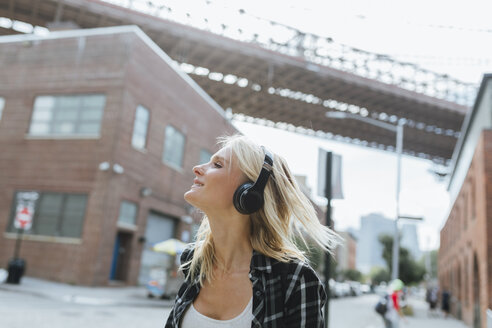 USA, New York City, Brooklyn, happy young woman listening to music with headphones in the city - BOYF01145