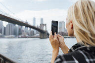 USA, New York City, Brooklyn, young woman at the waterfront taking a cell phone picture of Brooklyn Bridge - BOYF01151