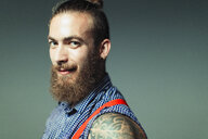 Portrait confident, cool male hipster with beard and shoulder tattoo - CAIF22367