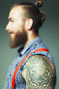 Close up hipster man with shoulder tattoo and beard - CAIF22394