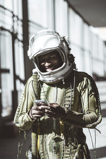 Smiling astronaut in spacesuit using smartphone - JCMF00020
