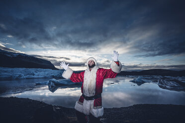 Iceland, man disguised as Santa Claus standing at a glacier raising his arms - OCMF00166