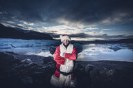 Iceland, portrait of a man disguised as Santa Claus standing at a glacier - OCMF00169