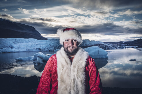 Iceland, portrait of a smiling man disguised as Santa Claus standing at a glacier - OCMF00172