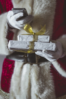 Santa Claus with smartphone and Christmas presents, partial view - JCMF00032