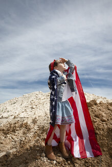 Girl standing on heap of soil holding American flag - ERRF00166