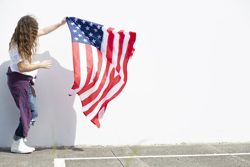 Girl holding American flag at white wall - ERRF00172