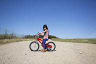 Girl with bicycle on path in remote landscape - ERRF00175