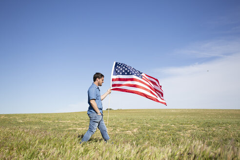 Man with American flag walking on field in remote landscape - ERRF00184