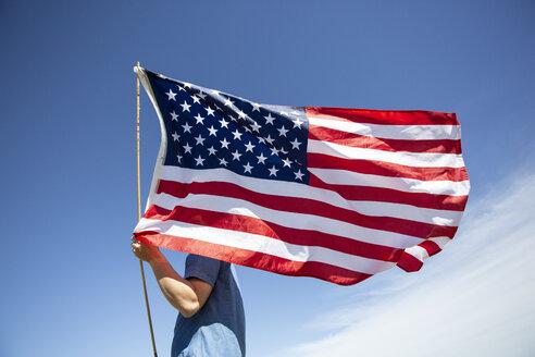 Man holding American flag under blue sky - ERRF00187