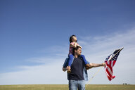 Man with daughter and American flag on field in remote landscape - ERRF00190