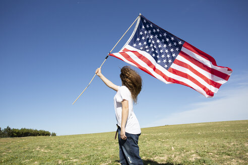 Girl holding American flag on field in remote landscape - ERRF00193