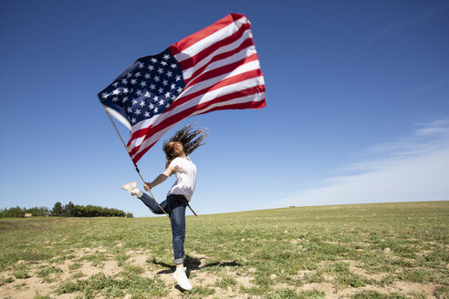 Happy girl holding American flag jumping on field in remote landscape - ERRF00196