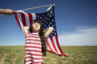 Hand holding American flag above girl on field in remote landscape - ERRF00199