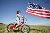 Girl with bicycle and American flag on field in remote landscape - ERRF00202